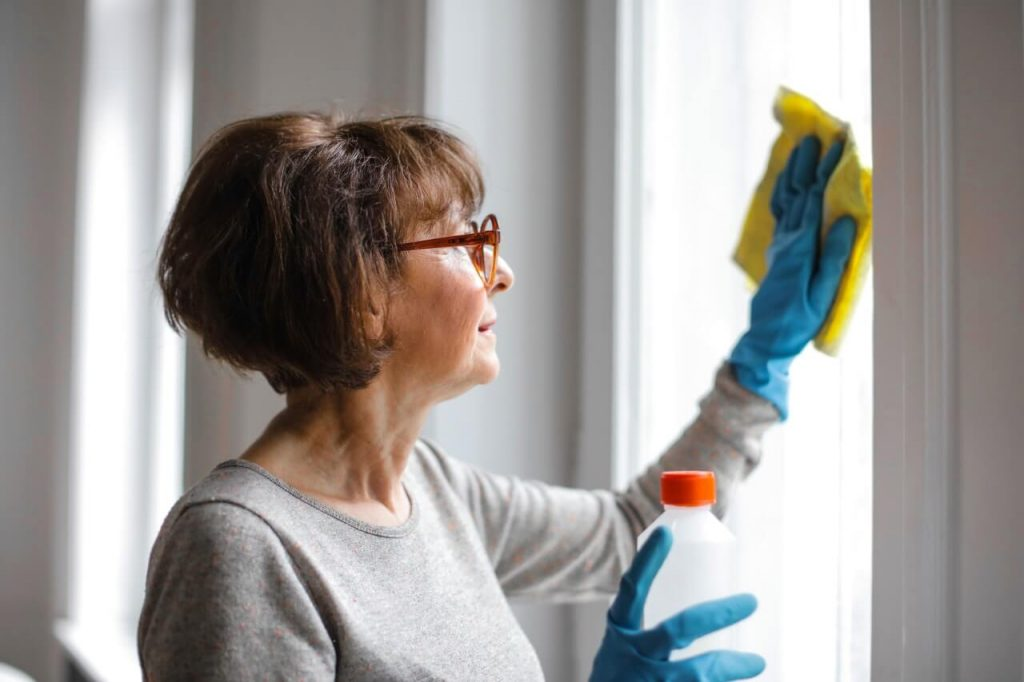 cleaning the windows with gloves and spray